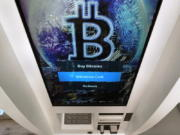 The Bitcoin logo appears on the display screen of a crypto currency ATM at the Smoker's Choice store, Tuesday, Feb. 9, 2021, in Salem, N.H.  After a wild week in which Bitcoin soared to new heights, Bitcoin is crossing the $50,000 mark. Bitcoin rallied last week as more companies signaled the volatile digital currency could eventually gain widespread acceptance as a means of payment for goods and services.