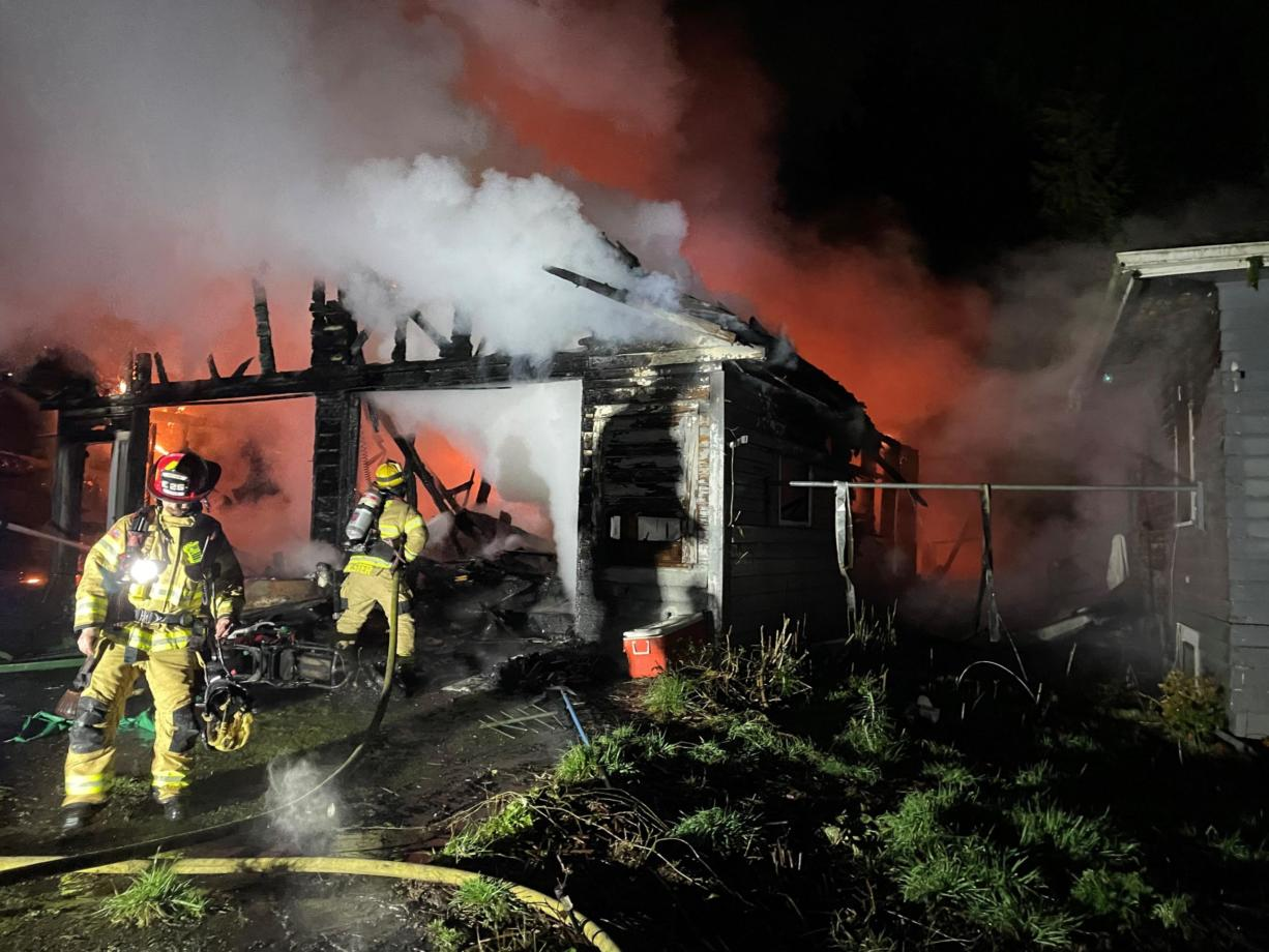 Crews from Clark-Cowlitz Fire Rescue battle a fire that damaged a detached garage and house at 2834 N. Smythe Road in Ridgefield late Monday night.