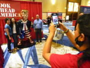 Conference attendees pose for a photo next to a statue of former president Donald Trump at the merchandise show at the Conservative Political Action Conference (CPAC) Saturday, Feb. 27, 2021, in Orlando, Fla.