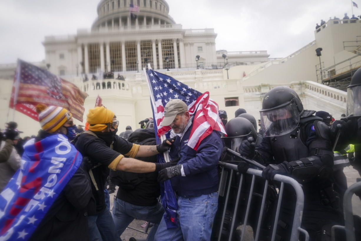 FILE - In this Jan. 6, 2021, file photo rioters try to break through a police barrier at the Capitol in Washington. People charged in the attack on the U.S. Capitol left behind a trove of videos and messages that have helped federal authorities build cases. In nearly half of the more than 200 federal cases stemming from the attack, authorities have cited evidence that an insurrectionist appeared to have been inspired by conspiracy theories or extremist ideologies, according to an Associated Press review of court records.
