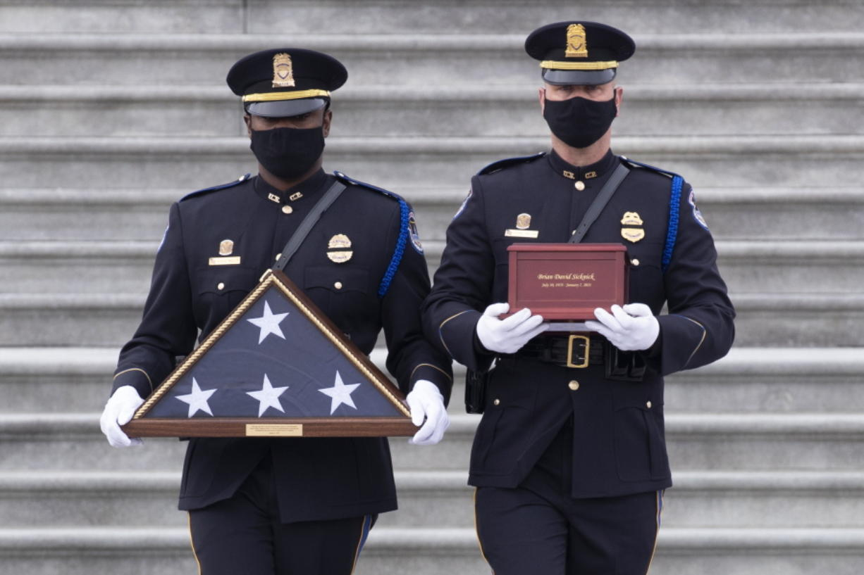 An honor guard carries an urn with the cremated remains of U.S. Capitol Police officer Brian Sicknick down the steps of the U.S. Capitol, Feb. 3 in Washington.