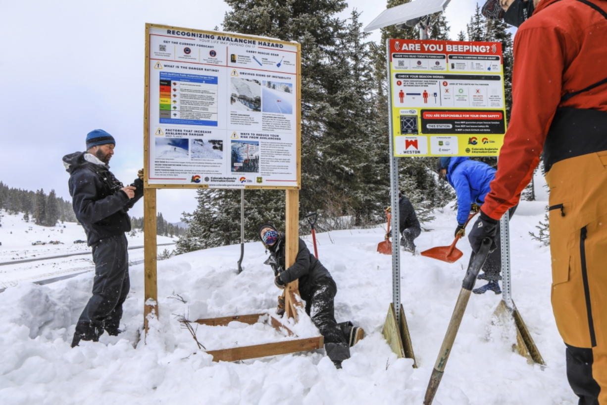 The avalanche danger and information sign is moved by U.S. Forest Snow Rangers, Kate DeMorest, right, and Bryce Parker, left, to accommodate the new beacon checkpoint sign, Monday, Jan. 25, at the Uneva Peak Trailhead atop Vail Pass, Colo. The new checkpoint informs backcountry users if their beacon is in transmit mode.