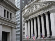 FILE - This Nov. 23, 2020 file photo shows the New York Stock Exchange, right, in New York.   Stocks are giving back some of their recent gains in early trading on Wall Street Wednesday, Feb. 17, not far below the record highs major indexes set in recent days.