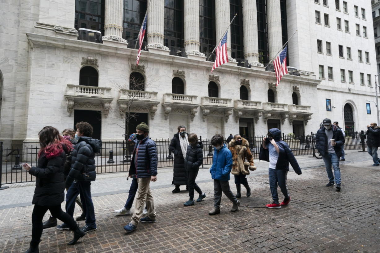A school group walks by the New York Stock Exchange, Tuesday, Feb. 23, 2021.  Major indexes are off to a mixed start on Wall Street as gains for banks and industrial companies are offset by losses in Big Tech stocks like Apple and Amazon. The S&P 500 was down 0.2% in the first few minutes of trading Wednesday, a day after it narrowly managed to break a five-day losing streak.