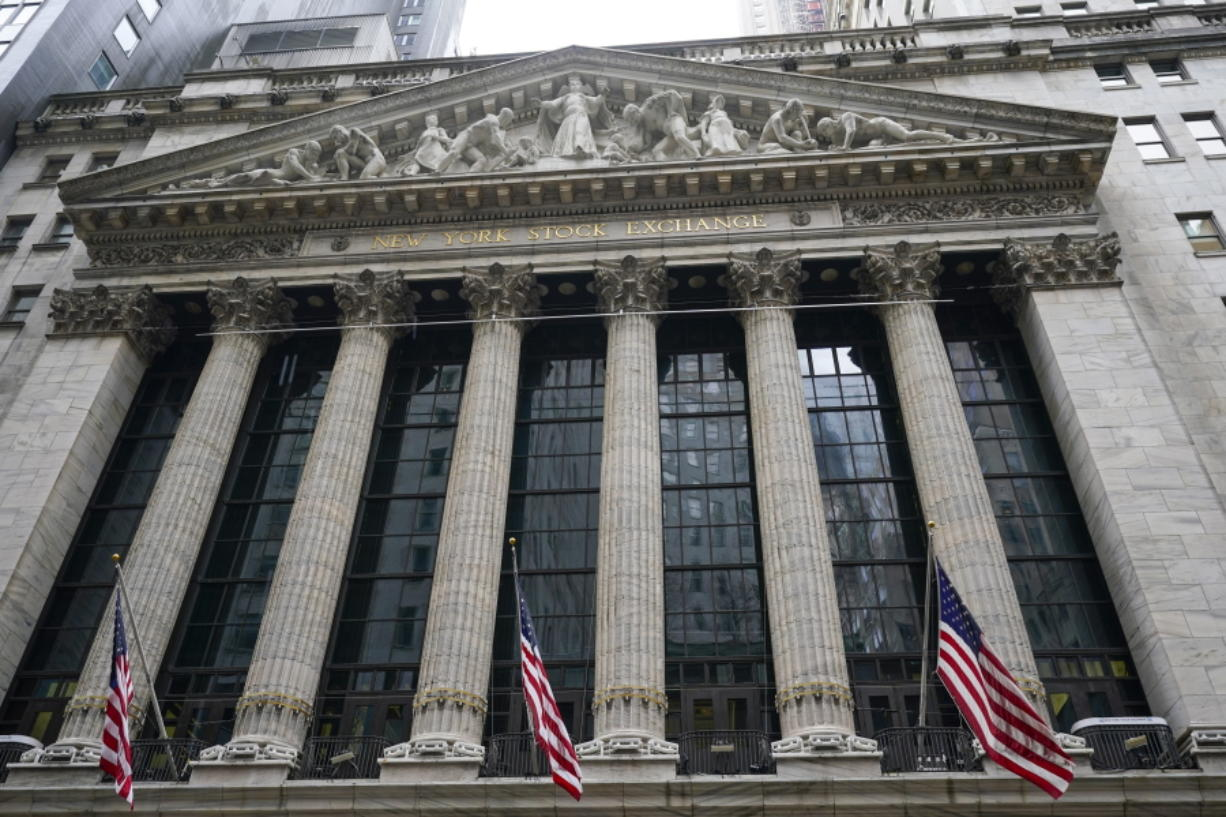 FILE - In this Tuesday, Feb. 16, 2021, American flags hang outside of the New York Stock Exchange in New York. Stocks are opening broadly lower on Wall Street, getting the week off to a sluggish start and continuing a losing streak. The S&P 500 gave up 0.6% in the early going Monday, Feb. 22 and other major indexes were also lower.