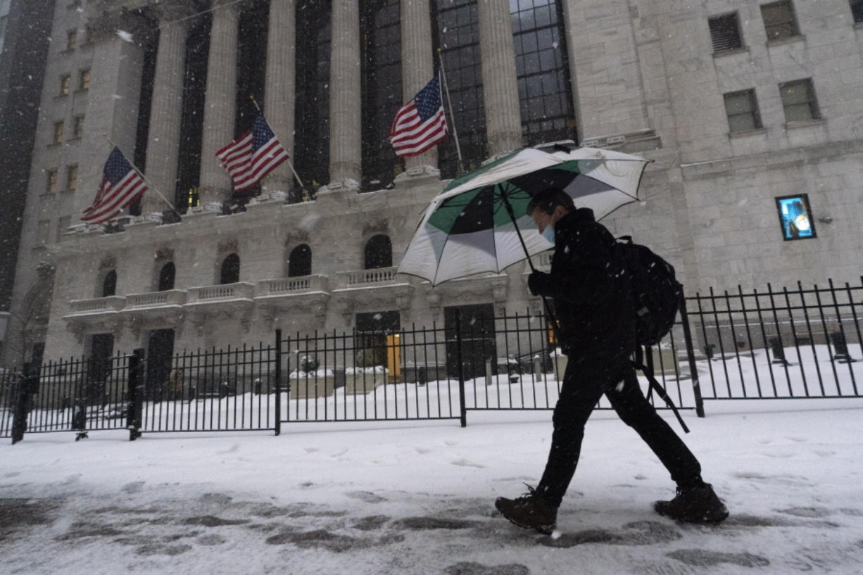 FILE - A man walks past the New York Stock Exchange during a snowstorm, Monday, Feb. 1, 2021, in New York.  Stocks are opening broadly lower on Wall Street and Treasury yields continued to climb. The S&P 500 index gave up 0.8% in the first few minutes of trading Thursday, Feb. 18,  and the tech-heavy Nasdaq was down slightly more, 1.1%.