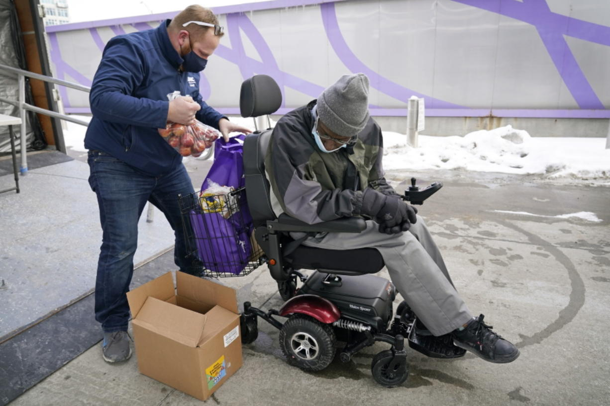 Des Moines Area Religious Council operations manager Joe Dolack, left, loads a Farmers to Families Food Box for Thomas Washington, of Des Moines, Iowa, at a mobile food pantry stop, Thursday, Feb. 18, 2021, in Des Moines, Iowa. Agricultural groups and anti-hunger organizations are pushing the Biden administration to continue the Farmers to Families Food Box program launched by President Donald Trump that spent $6 billion to prevent farmers from plowing under food and instead provide it to millions of Americans left reeling by the coronavirus pandemic.