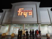 FILE- In this Oct. 21, 2009 file photo, a small crowd begins to gather outside a Fry's Electronics store in Renton, Wash. The electronics chain is permanently closing, citing the struggles it faced as a retailer during the coronavirus pandemic. The company, which was in business for 36 years, had 31 stores in nine states. Fry's Electronics Inc. said it stopped regular operations and began the wind-down process of its business on Wednesday, Feb. 24, 2021. (AP Photo/Ted S.
