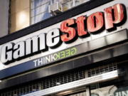 Pedestrians pass a GameStop store Thursday in the Manhattan borough of New York. GameStop stock had rocketed from below $20 to more than $400 this month as a volunteer army of investors on social media challenged big institutions who has placed market bets that the stock would fall.