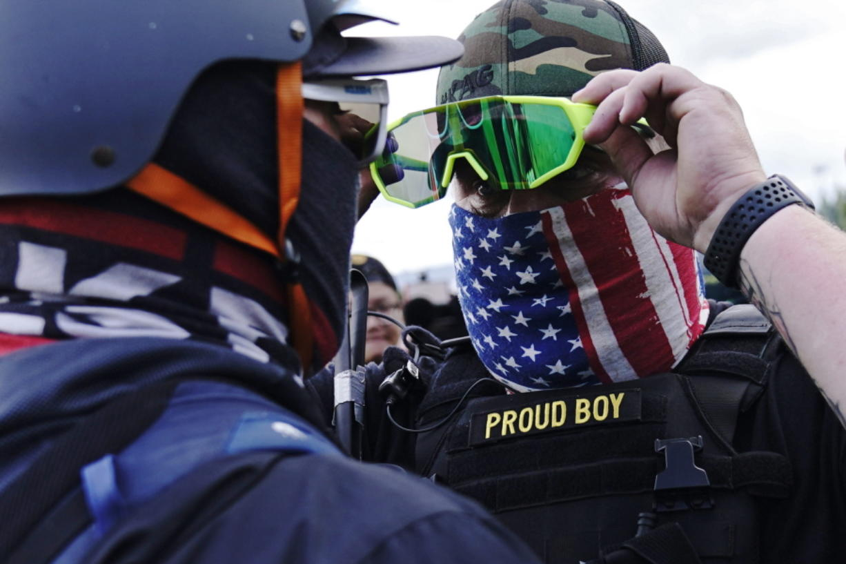 FILE - In this Sept. 26, 2020, file photo, member of the Proud Boys, right, stands in front of a counter protester as members of the Proud Boys and other right-wing demonstrators rally, in Portland. In its annual report set to be released Monday, Feb. 1, 2021, the Southern Poverty Law Center said it identified 838 active hate groups operating across the U.S. in 2020.