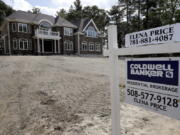 FILE - In this Sept. 3, 2019 file photo a sign rests in front of a newly constructed home, in Westwood, Mass. U.S. home prices rose in April for the eighth straight month, even as sales have stumbled, a sign the coronavirus outbreak has had little impact on real estate values. The S&P CoreLogic Case-Shiller 20-city home price index climbed 4% in April, the largest gain since December 2018, up from 3.9% in March.