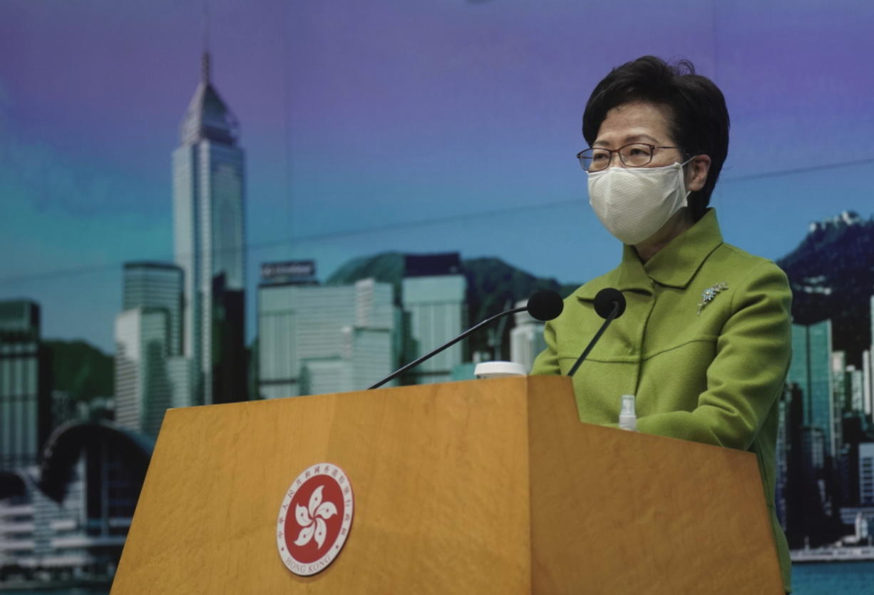 """FILE - In this Jan. 26, 2021, file photo, Hong Kong Chief Executive Carrie Lam listens to reporters' questions during a press conference in Hong Kong. Hong Kong leader Carrie Lam said Tuesday, Feb. 23, that it was """"crystal clear"""" that electoral reform is necessary, a day after a top Beijing official signaled major changes would be coming to ensure the semi-autonomous city is run by """"patriots."""