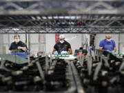 FILE - In this May 13, 2020, file photo, Ford Motor Co., line workers put together ventilators that the automaker is assembling at the Ford Rawsonville plant in Ypsilanti Township, Mich. U.S. industrial production increased 0.4% in November with manufacturing receiving a boost from a rebound in output at auto plants after three months of declines. The Federal Reserve reported Tuesday, Dec. 15 that the November gain in industrial output followed an even stronger 0.9% increase in October.