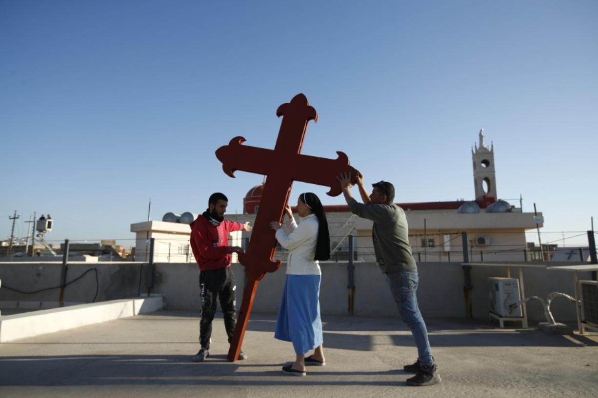 Iraqi Christians place a cross on a church in Qaraqosh, Iraq, on Feb. 22.