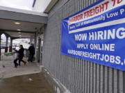 """FILE - In this Dec. 10, 2020 file photo, a """"Now Hiring"""" sign hangs on the front wall of a Harbor Freight Tools store in Manchester, N.H.   U.S. employers cut back sharply on hiring in December, particularly in pandemic-hit industries such as restaurants and hotels, as soaring virus infections and government restrictions weakened the economy that month. The number of available jobs rose slightly and layoffs fell, according to the Labor Department's Tuesday report, known as the Job Openings and Labor Turnover Survey, or JOLTS."""