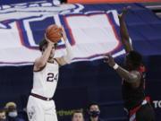 Gonzaga forward Corey Kispert shoots as Loyola Marymount guard Eli Scott defends during the second half of an NCAA college basketball game in Spokane, Wash., Saturday, Feb. 27, 2021.