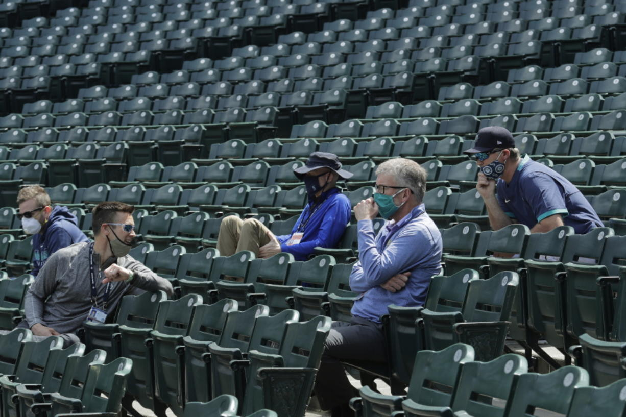 Seattle Mariners general manager Jerry Dipoto, second from left, manager Scott Servais, right, and team president and CEO Kevin Mather, second from right, watch a practice in July 2020. Dipoto and Servais are doing damage control with players who were directly mentioned or referenced by Mather in an online video that led to his resignation. (Ted S.