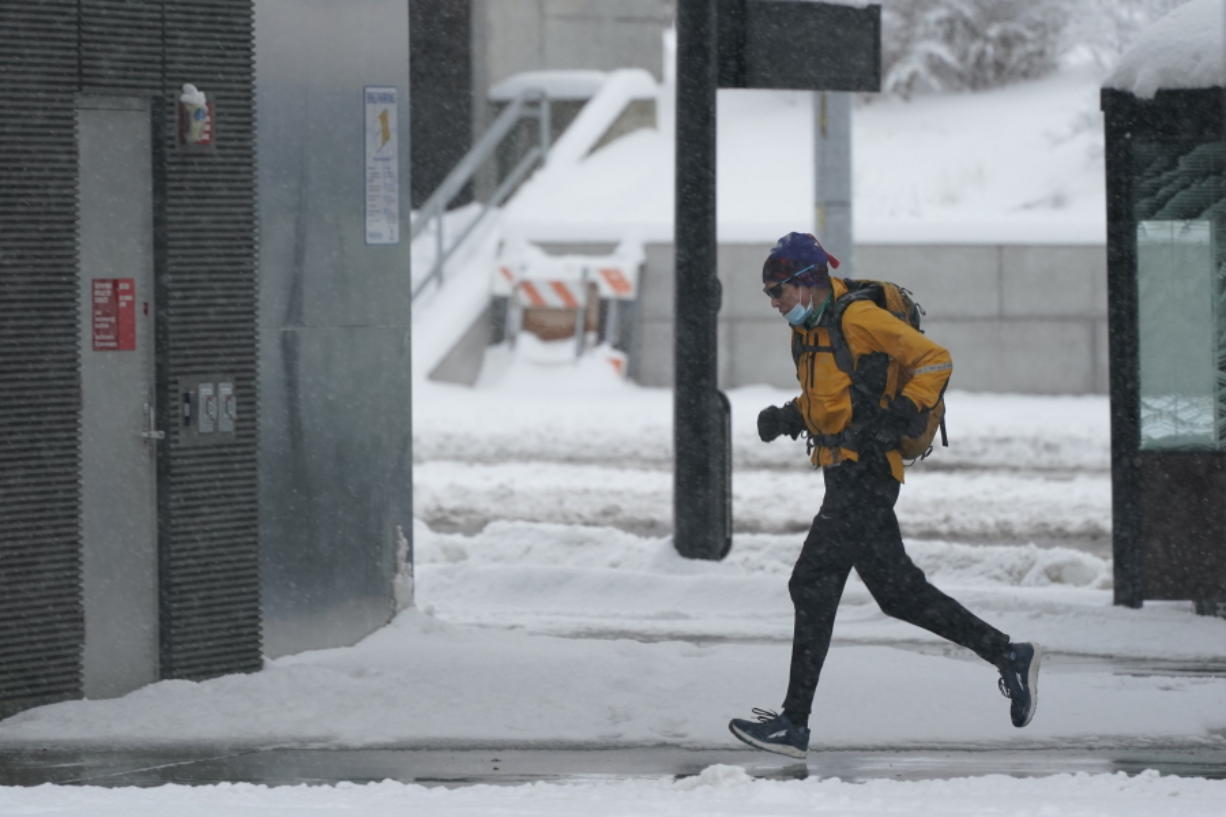 A person runs in the snow, Saturday, Feb. 13, 2021, on the University of Washington campus in Seattle. Winter weather was expected to continue through the weekend in the region.(AP Photo/Ted S.