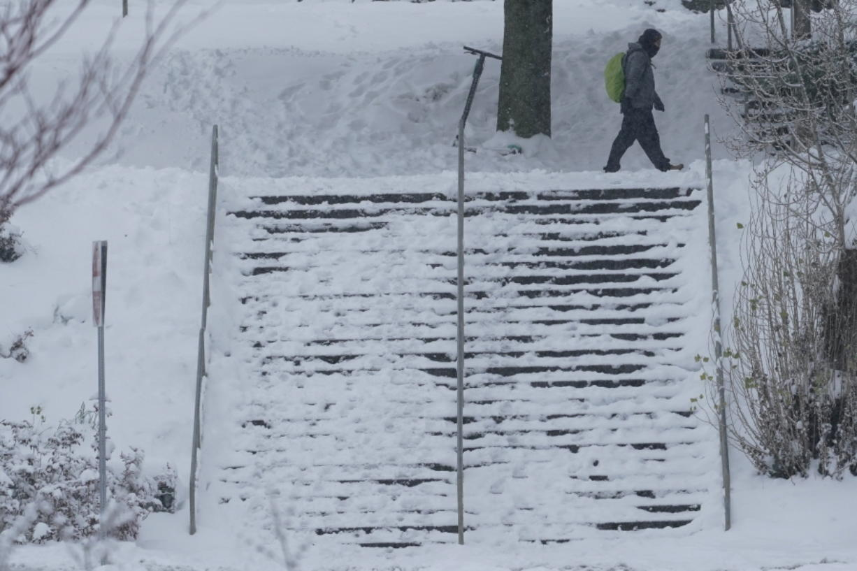 A pedestrian walks near a snow-covered staircase, Saturday, Feb. 13, 2021, on the University of Washington campus in Seattle. Winter weather was expected to continue through the weekend in the region.(AP Photo/Ted S.