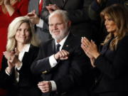 FILE - In this Feb. 4, 2020 file photo, Rush Limbaugh reacts as first Lady Melania Trump, and his wife Kathryn, applaud, as President Donald Trump delivers his State of the Union address to a joint session of Congress on Capitol Hill in Washington.  Limbaugh, the talk radio host who became the voice of American conservatism, has died.
