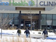 FILE - In this Tuesday, Feb. 9, 2021 file photo, law enforcement personnel walk toward the Allina Health clinic where multiple people were shot in Buffalo, Minn. Doctors say they're facing increasing threats of violence for refusing to prescribe opioids or trying to wean patients off the addictive painkillers. The issue was underscored by Tuesday's shooting at the Minnesota clinic.