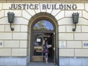 FILE - In this May 28, 2020 file photo a woman enters the Oregon Department of Justice building in Salem, Ore. The Oregon Supreme Court, ruling in a murder case, has upheld that a defendant may be acquitted by a nonunanimous verdict. This comes months after the U.S. Supreme Court ruled that guilty verdicts must be unanimous. Oregon is the only state that allows split jury verdicts -- but only for not guilty verdicts.