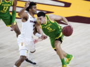 Oregon guard Chris Duarte (5) drives past Arizona State guard Remy Martin (1) during the first half of an NCAA college basketball basketball game, Thursday, Feb. 11, 2021, in Tempe, Ariz.