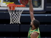 Oregon guard LJ Figueroa, top, dunks against California during the second half of an NCAA college basketball game in Berkeley, Calif., Saturday, Feb. 27, 2021.