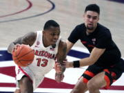 Arizona guard James Akinjo (13) drives by Oregon State guard Jarod Lucas during the first half of an NCAA college basketball game, Thursday, Feb. 11, 2021, in Tucson, Ariz.