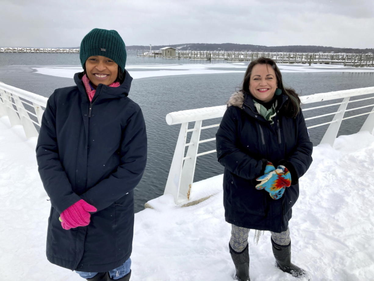 Activists Tyasha Harrison, left, and Holly T. Bird pose along the Grand Traverse Bay waterfront in Traverse City, Mich., Feb. 13, 2021. They are among local residents who have criticized a county commissioner for displaying a gun during an online meeting. The official's provocative act came as a caller was raising concerns about right-wing extremism. Some activists say the incident is among many showing that Michigan's seemingly tranquil north has some of the same racial and cultural divides that have ignited protests and violence in bigger cities.