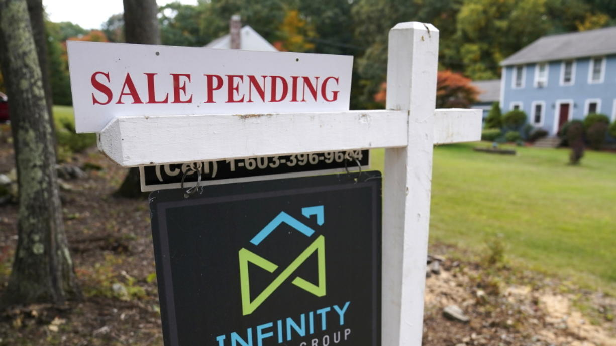 FILE - In this Sept. 29, 2020 file photo, a sale pending sign is displayed outside a residential home for sale in East Derry, N.H. The number of Americans signing contracts to buy homes fell for the second straight month as lack of available homes continue to stifle house hunters. The National Association of Realtors said Monday, Nov. 30 that its index of pending sales fell 1.1%, to 128.9 in October, down from a reading of 130.3 in September.