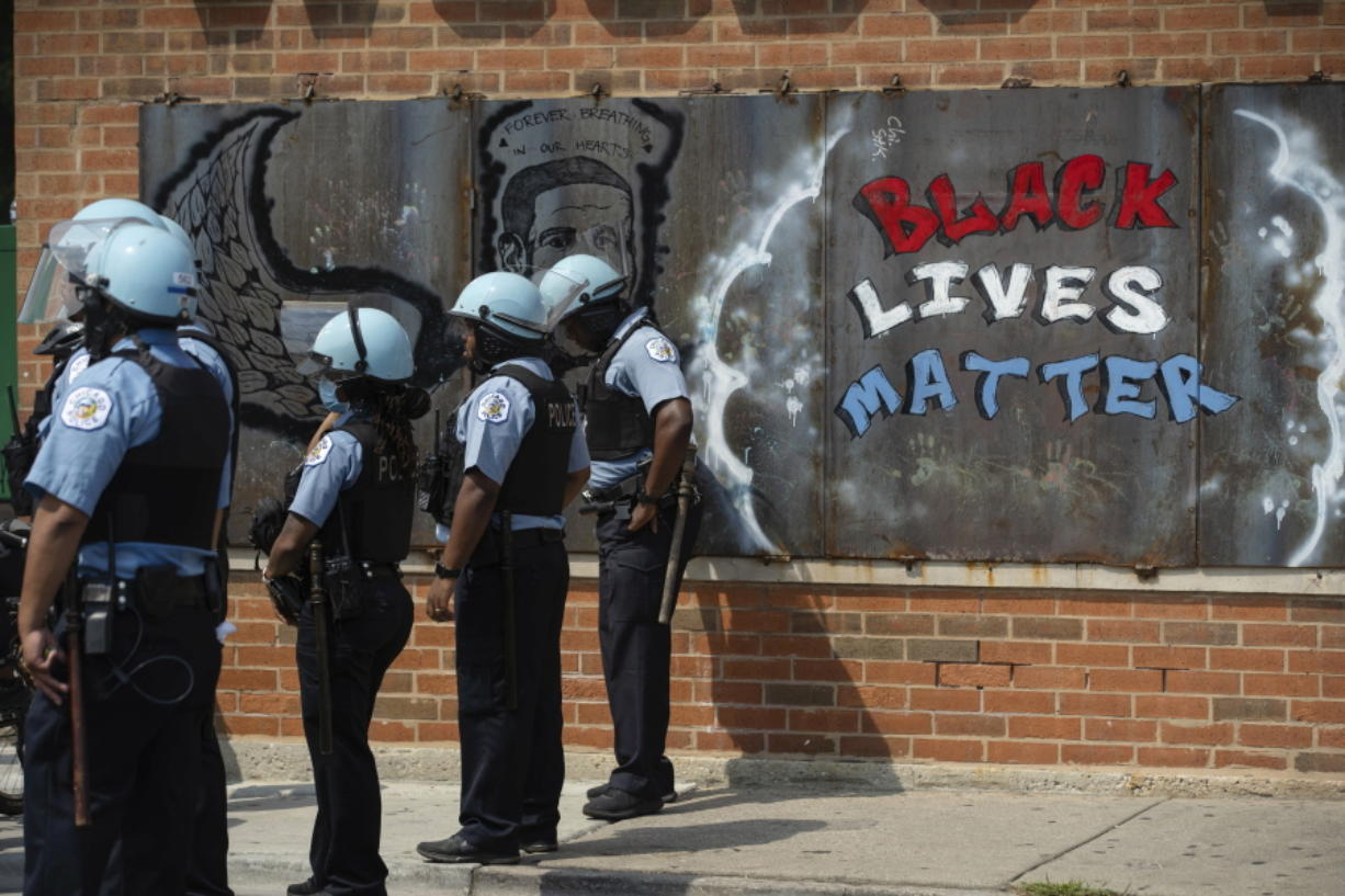 FILE - In this Aug. 15, 2020, file photo, police officers stand beside a mural for George Floyd in the Chicago neighborhood of Bronzeville during an anti-police brutality protest. In the last decade, high-profile police killings  -- including Floyd -- have shaken the nation and led to widespread protests and calls for reform, including hiring more nonwhite and female officers.
