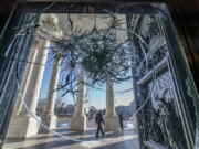 FILE - In this Jan. 12, 2021, file photo, shattered glass from the attack on Congress by a pro-Trump mob is seen in the doors leading to the Capitol Rotunda, in Washington. (AP Photo/J.