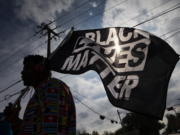 FILE - In this Dec. 12, 2020, file photo, MD Crawford carries a Black Lives Matter flag before a march in La Marque, Texas to protest the shooting of Joshua Feast, 22, by a La Marque police officer. A financial snapshot shared exclusively with The Associated Press shows the Black Lives Matter Global Network Foundation raked in just over $90 million last year.