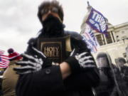 A man holds a Bible as Trump supporters gather outside the Capitol in Washington on Jan. 6.