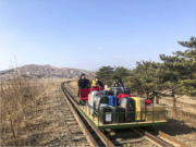 In this image taken from a video released by Russian Foreign Ministry Press Service Thursday, Feb. 25, 2021, a group of Russian diplomats push hand-pushed rail trolley with their children and suitcases to the border with Russia. A group of Russian diplomats and their family members returned to Russia from North Korea on a hand-pushed rail trolley on Thursday because of COVID-19 restrictions in the country, Russia's Foreign Ministry said in a Facebook post.