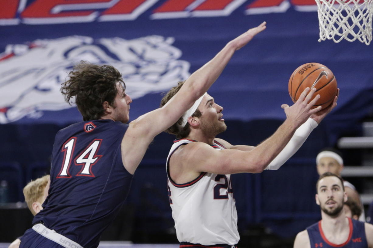 Gonzaga forward Corey Kispert, right, shoots in front of Saint Mary's forward Kyle Bowen during the first half of an NCAA college basketball game in Spokane, Wash., Thursday, Feb. 18, 2021.