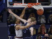Gonzaga guard Aaron Cook, left, dunks over San Diego forward Ben Pyle during the second half of an NCAA college basketball game in Spokane, Wash., Saturday, Feb. 20, 2021.