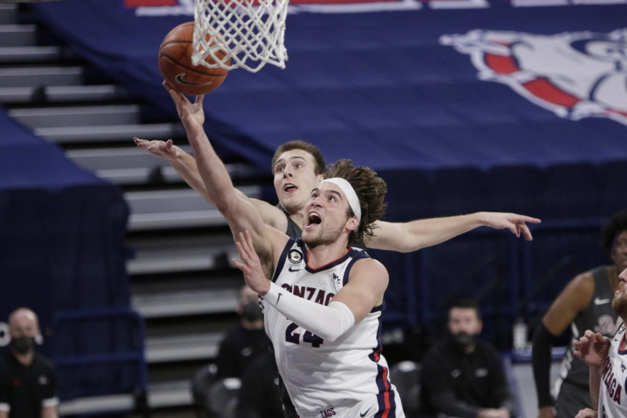 Gonzaga forward Corey Kispert, front, shoots in front of Santa Clara forward Josip Vrankic during the second half of an NCAA college basketball game in Spokane, Wash., Thursday, Feb. 25, 2021.