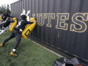 Pacific Lutheran players take part in a blocking drill against a storage container during football practice Tuesday in Tacoma. For all the attention heaped on the FBS level of college football last fall as it tried to play, it will not be the only college football during the 2020-21 sports calendar as a handful of NCAA Division III and NAIA programs begin some form of a winter/spring season Saturday. (Photos by Ted S.