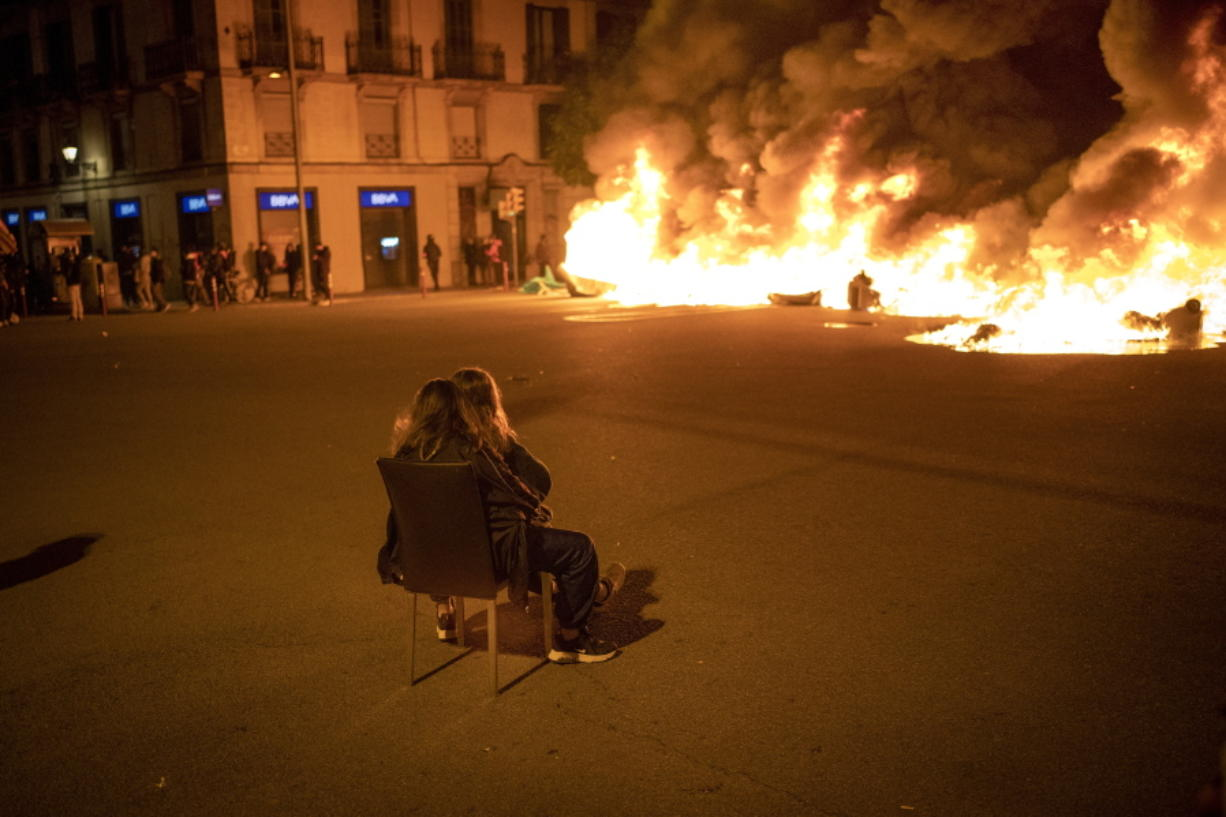 Two women sit on a chair in front of burning barricades made by demonstrators during a protest condemning the arrest of rap singer Pablo Hasel in Barcelona, Spain, Friday.