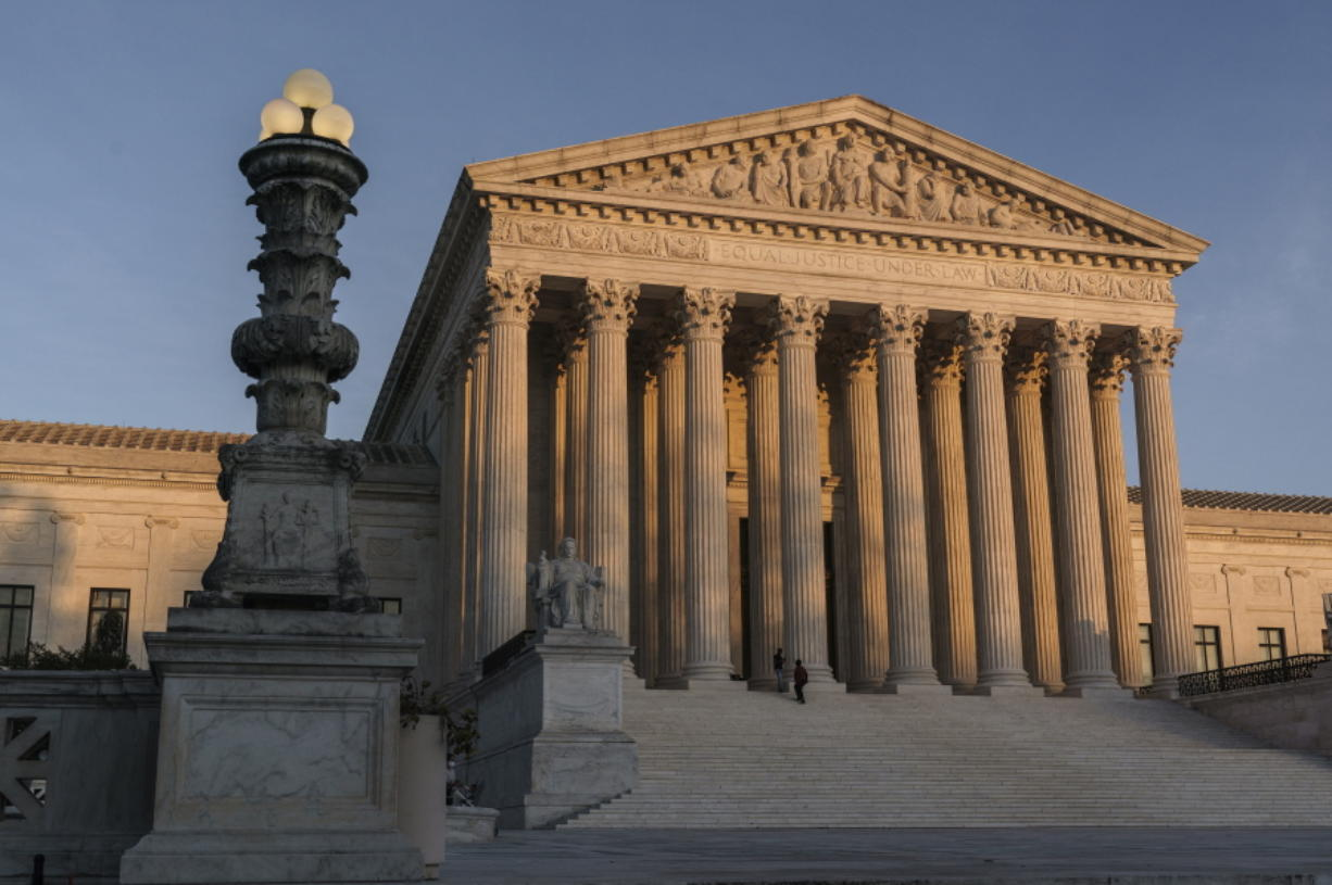 FILE - In this Friday, Nov. 6, 2020 file photo, The Supreme Court is seen at sundown in Washington. The Supreme Court is telling California it can't enforce a ban on indoor church services because of the coronavirus pandemic. The high court issued orders late Friday, Feb. 5, 2021 in two cases where churches had sued over coronavirus-related restrictions in the state. (AP Photo/J.