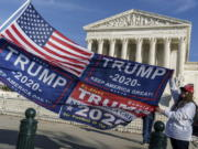 FILE - In this Dec. 11, 2020 file photo, Kathy Kratt of Orlando, Fla., displays her Trump flags as she and other protesters demonstrate their support for President Donald Trump at the Supreme Court in Washington. The Supreme Court has formally rejected a handful of cases related to the 2020 election, including disputes from Pennsylvania that had divided the justices just before the election. The cases the justices rejected involved election challenges filed by former President Donald Trump and his allies in five states President Joe Biden won: Arizona, Georgia, Michigan, Pennsylvania and Wisconsin.(AP Photo/J.