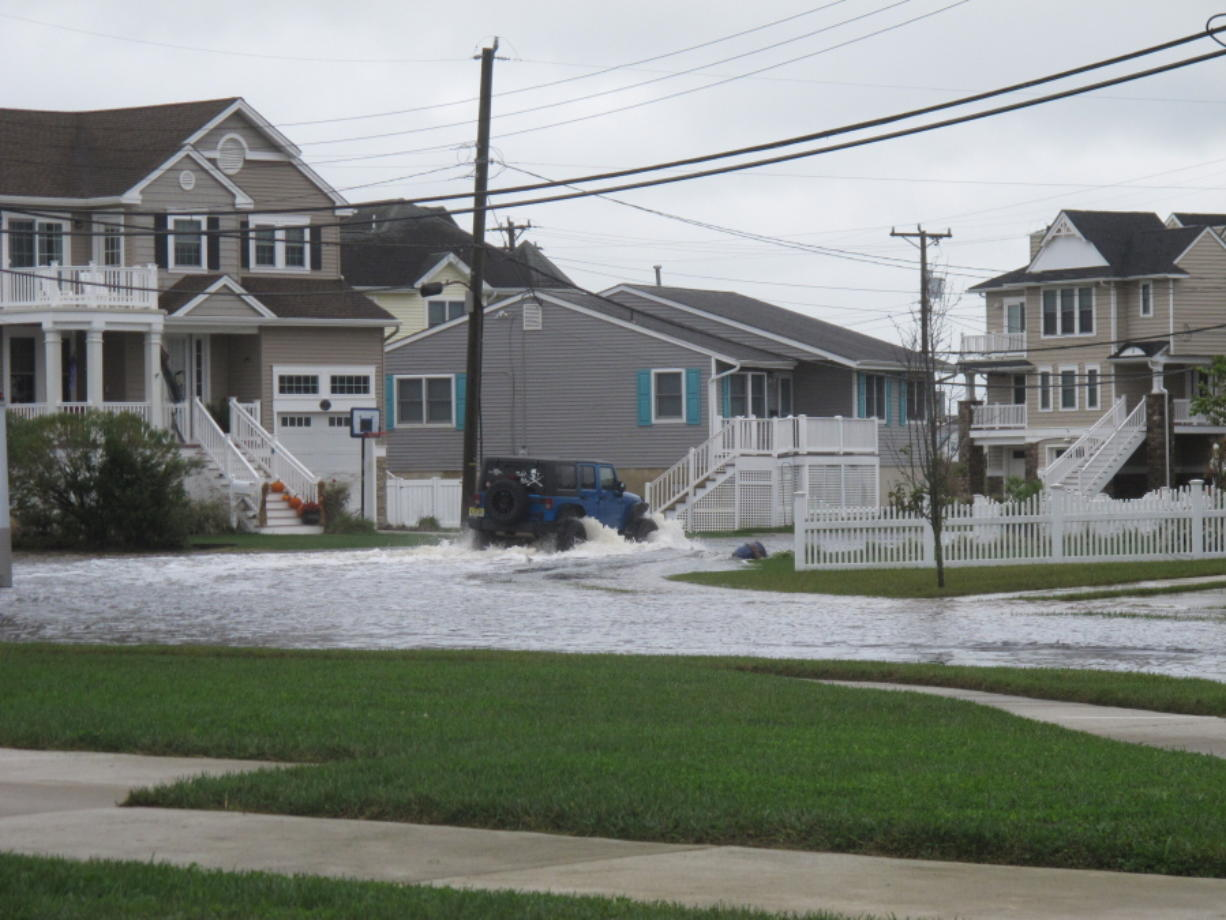 A vehicle kicks up a wake as it drives through a flooded street in Ocean City, N.J. on Oct. 30, 2020. The city is dealing with the costs of rising sea levels, both in monetary terms and in the disruption that recurring flooding brings.