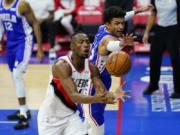 Portland Trail Blazers' Harry Giles III, left, and Philadelphia 76ers' Matisse Thybulle chase after a loose ball during the first half of an NBA basketball game, Thursday, Feb. 4, 2021, in Philadelphia.