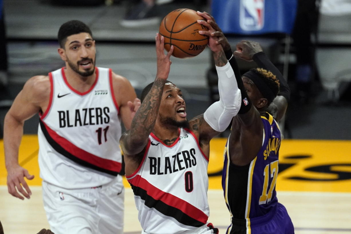 Los Angeles Lakers guard Dennis Schroder (17) blocks a shot by Portland Trail Blazers guard Damian Lillard (0) during the first half of an NBA basketball game Friday, Feb. 26, 2021, in Los Angeles. (AP Photo/Mark J.