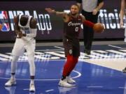Portland Trail Blazers guard Damian Lillard (0) reacts to a call of a jump ball as Dallas Mavericks forward Dorian Finney-Smith (10) celebrates during the first half of an NBA basketball game in Dallas, Sunday, Feb. 14, 2021.
