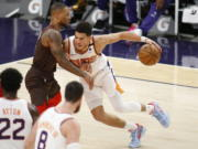 Phoenix Suns' Devin Booker muscles his way towards the basket against Portland Trail Blazers' Damien Lillard during the first half of an NBA basketball game Monday, Feb. 22, 2021, in Phoenix.
