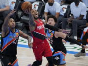 Portland Trail Blazers guard Damian Lillard (0) shoots between Oklahoma City Thunder center Al Horford (42) and center Isaiah Roby (22) in the second half of an NBA basketball game Tuesday, Feb. 16, 2021, in Oklahoma City.