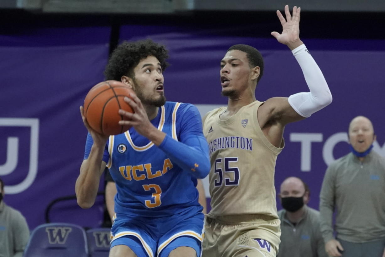 UCLA guard Johnny Juzang, left, looks to shoot around the defense of Washington guard Quade Green (55) during the second half of an NCAA college basketball game, Saturday, Feb. 13, 2021, in Seattle. (AP Photo/Ted S.